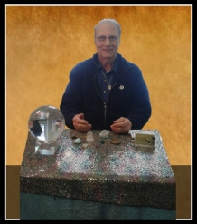 A Salem psychic with a strong connection to spirit that has been in Salem MA for Over 10 years sitting at a table with a crystal ball.